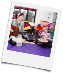 Photo: Children and carers taking part in a music therapy session courtesy of Haven House Children's Hospice